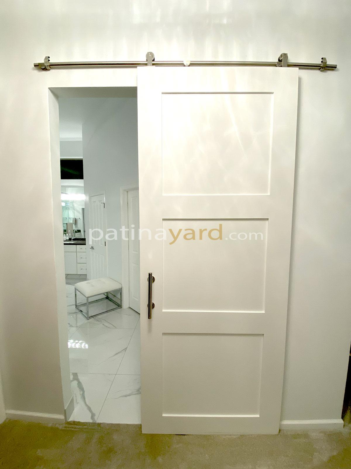 painted white shaker style barn door with stainless steel hardware